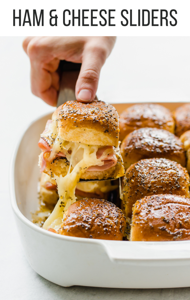 Hand pulling out a ham and cheese slider from a white dish