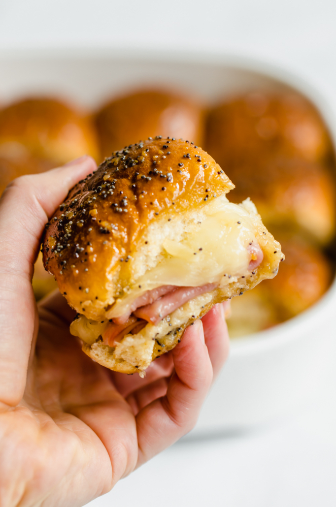 Hand holding ham & cheese sliders