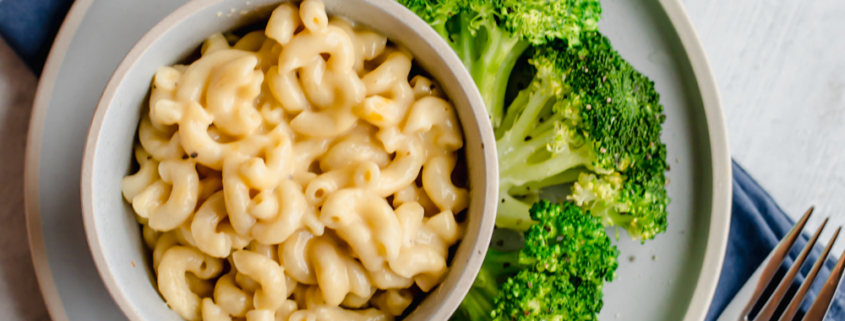 whole wheat mac and cheese in bowls on white plates with steamed broccoli on the side