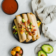 Chicken and Cheese Taquitos piled on a serving platter with avocado lime salsa on top. Other toppings are nearby, like avocado, tomatoes, and salsa.