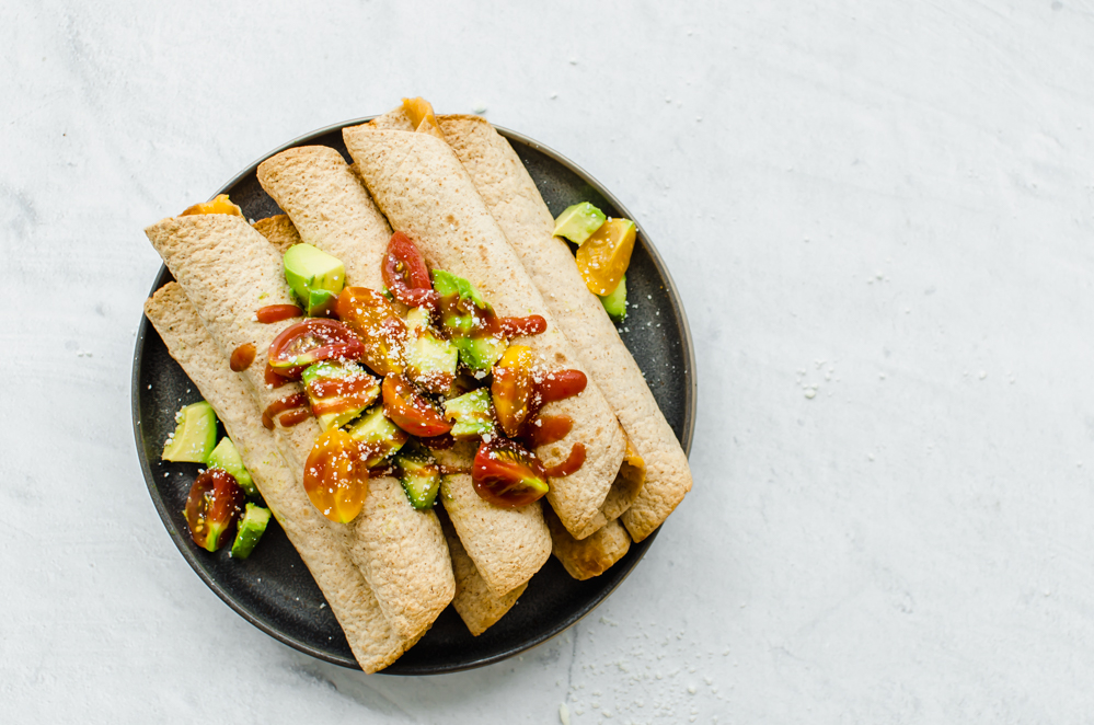Chicken and Cheese Taquitos piled on a serving platter with avocado lime salsa on top