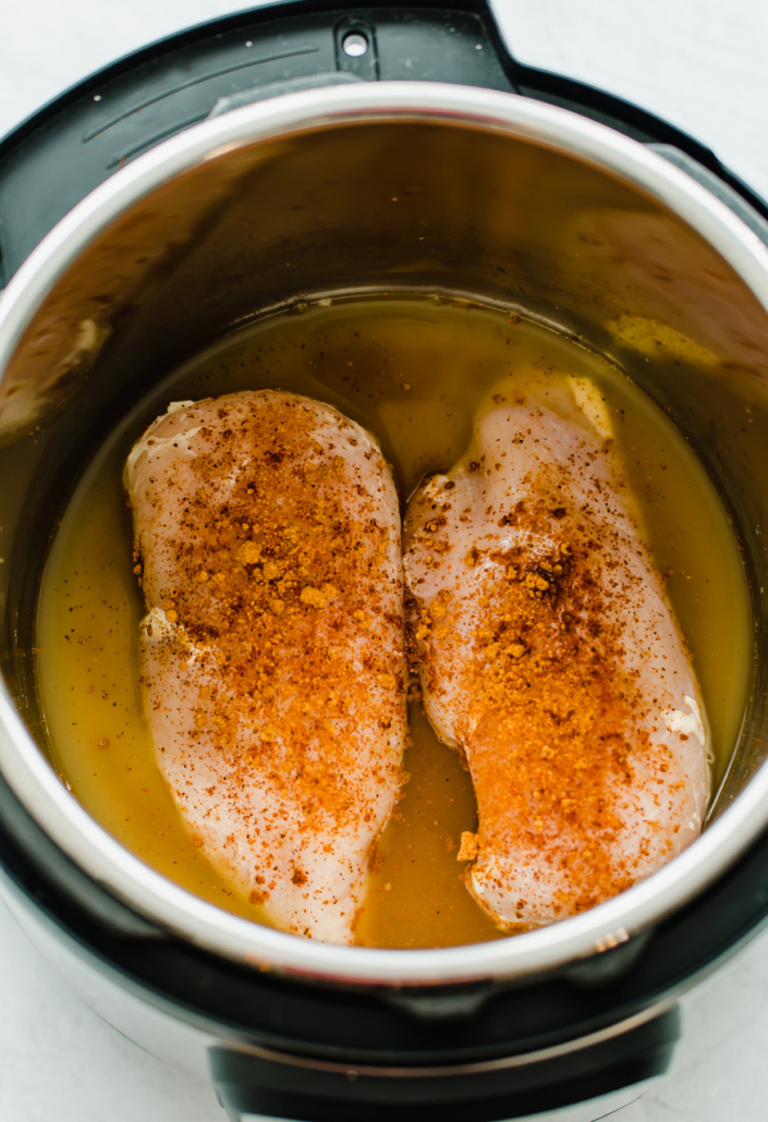 Chicken breasts with seasoning and broth in an Instant Pot