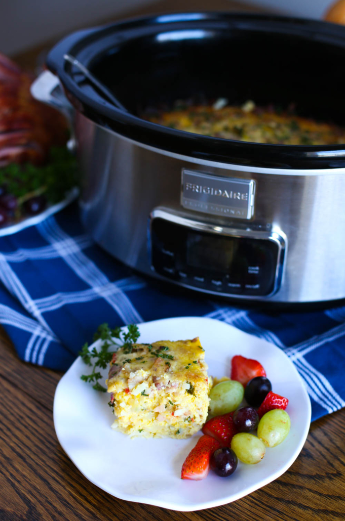 Breakfast Casserole slice on a plate with fruit and a slow cooker in the background