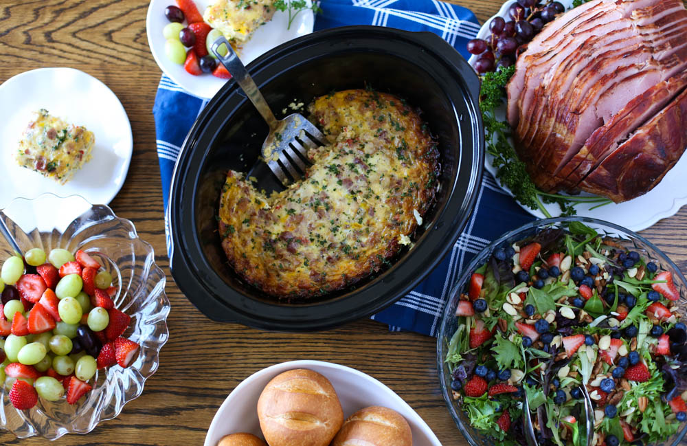 Slow cooker with hash brown casserole, a ham, salad, fruit salad, and plates on a wooden table