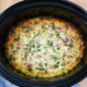 Breakfast Casserole in a Crockpot on a wooden cutting board