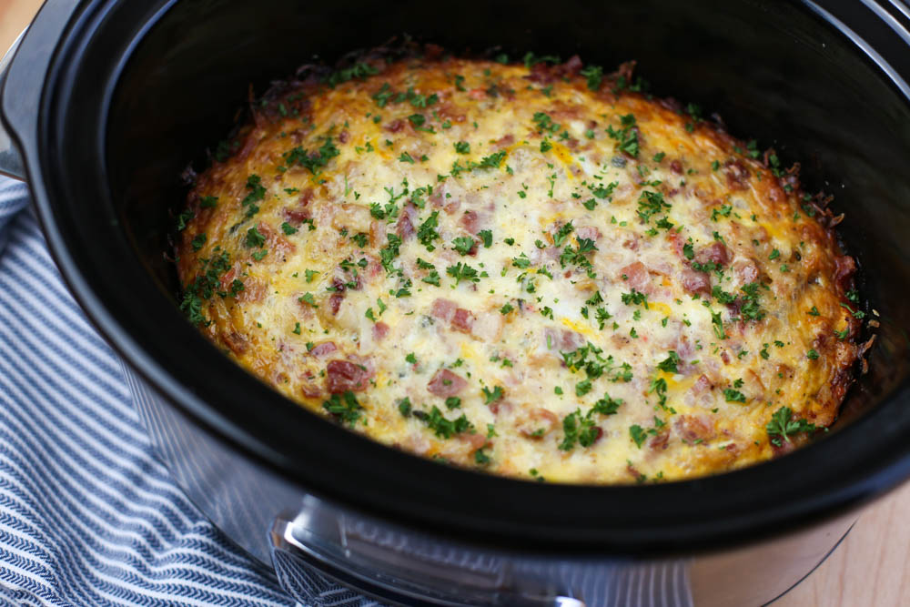 Make ahead Breakfast Casserole in a Crockpot on a wooden cutting board for serving at an Easter brunch.