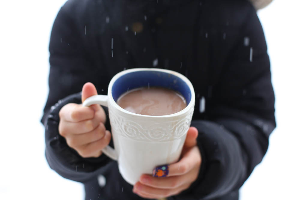 hands holding ghirardelli hot chocolate