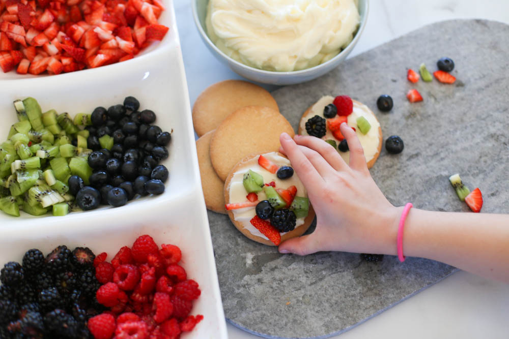 Hand grabbing a fruit pizza cookie