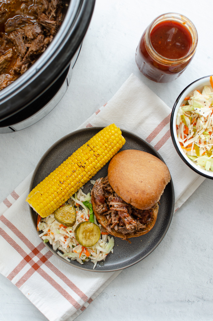 BBQ Beef Sandwiches on a plate with corn and coleslaw