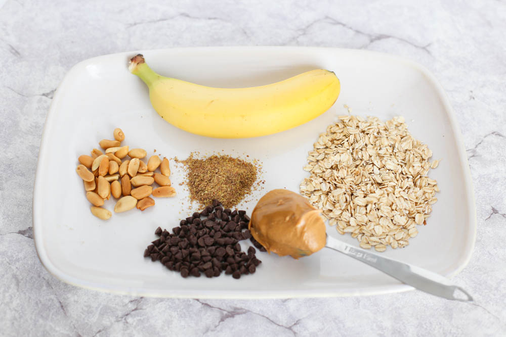 bananas, peanuts, flaxseed, mini chocolate chips, peanut butter, and rolled oats on a plate