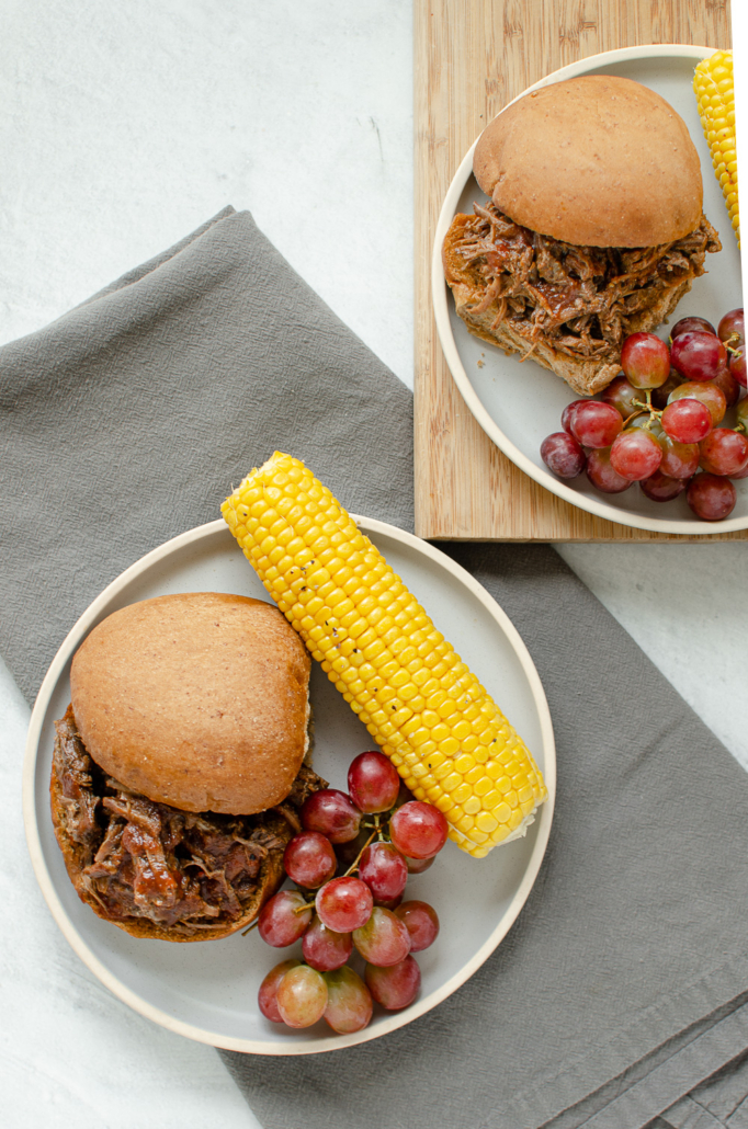 BBQ shredded beef sandwich on plates with corn and grapes