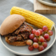 BBQ shredded beef sandwich on a plate with corn and grapes