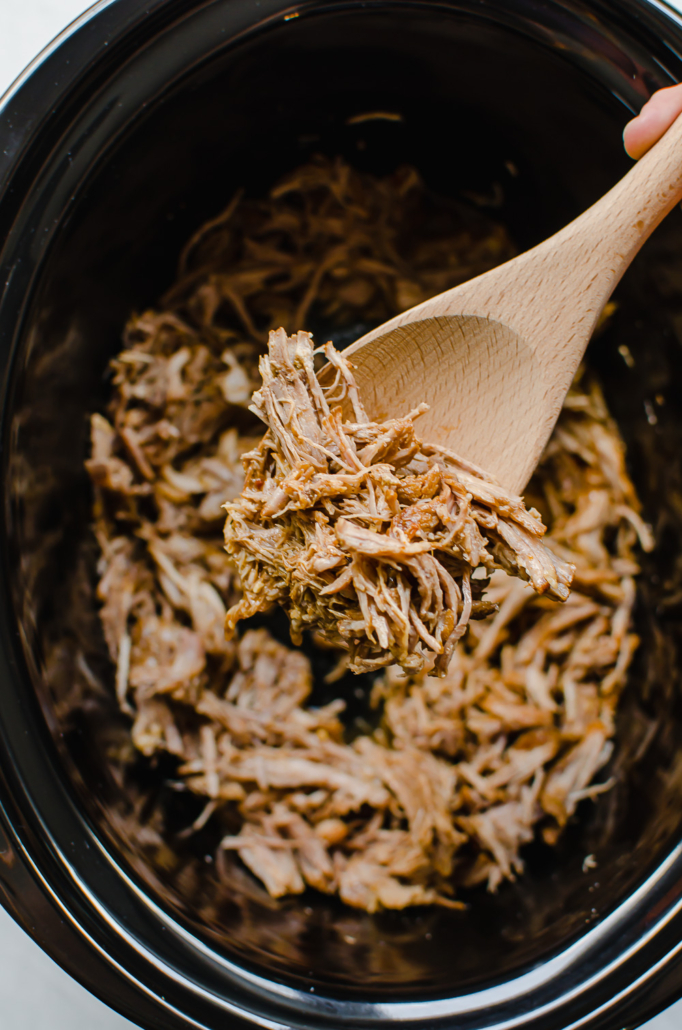Cooked pork carnitas on a wooden spoon coming out of the slow cooker