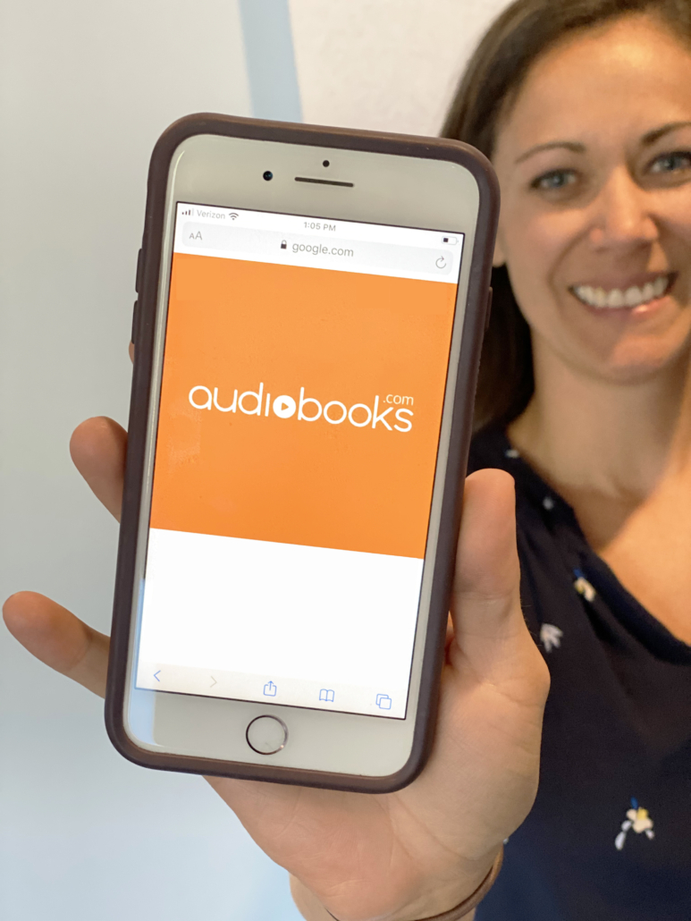 Polly Conner holding phone with audiobook.com logo