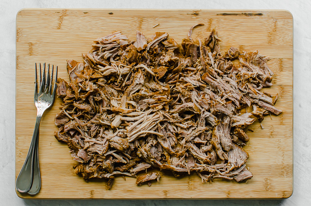 Shredded pork shoulder on wooden cutting board