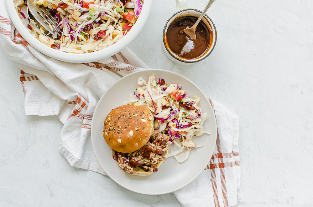 Slow Cooker pulled pork on a white plate with coleslaw