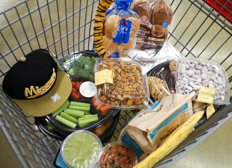 shopping cart filled with tailgating food and swag