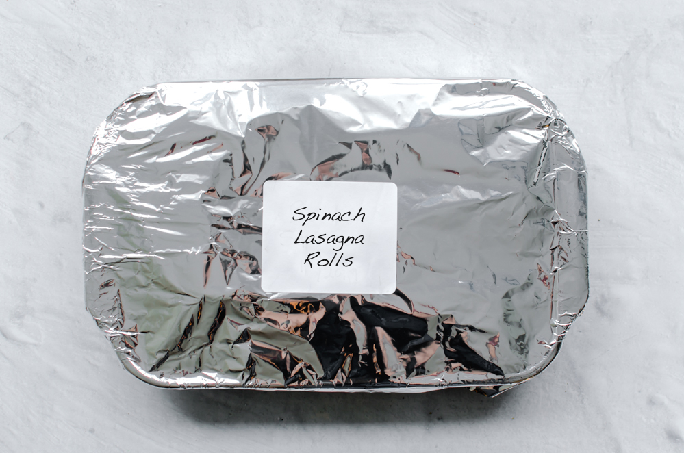 Spinach Lasagna Rolls in a freezer container covered with foil