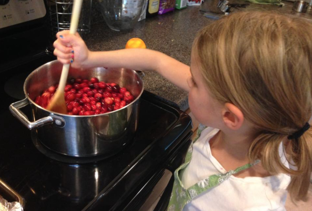 girl making homemade cranberry sauce