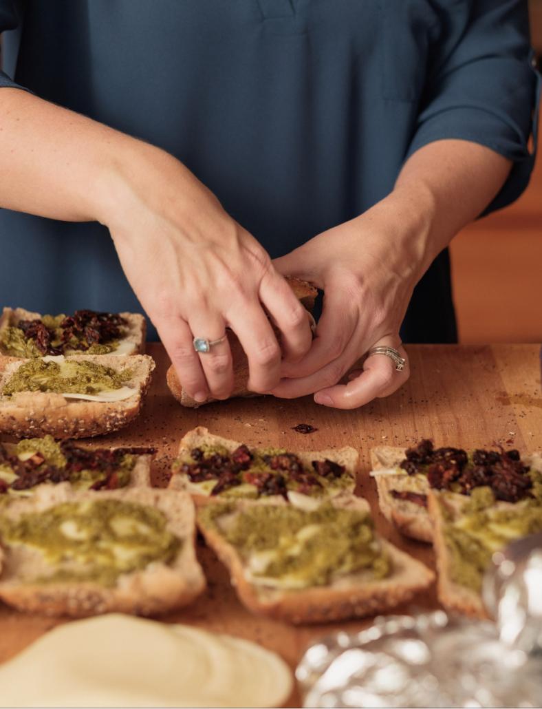 Hands assembling turkey pesto paninis