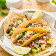 Crispy carnitas tacos in a metal dish with white bowls of toppings on the side.