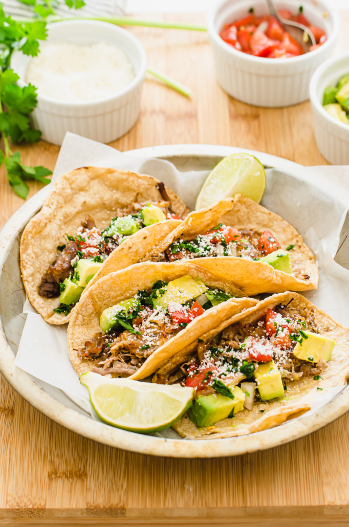 Freezer meal Instant Pot Crispy Carnitas on a plate with mexican toppings.