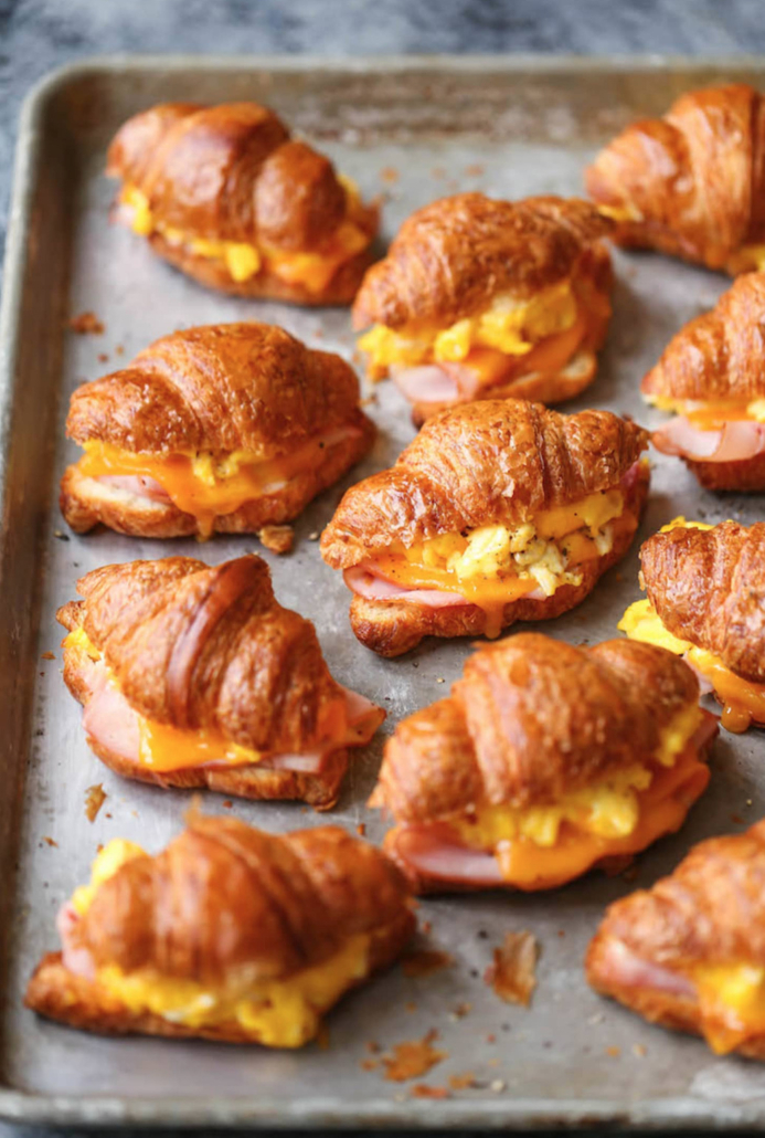 croissant breakfast sandwiches on a baking sheet