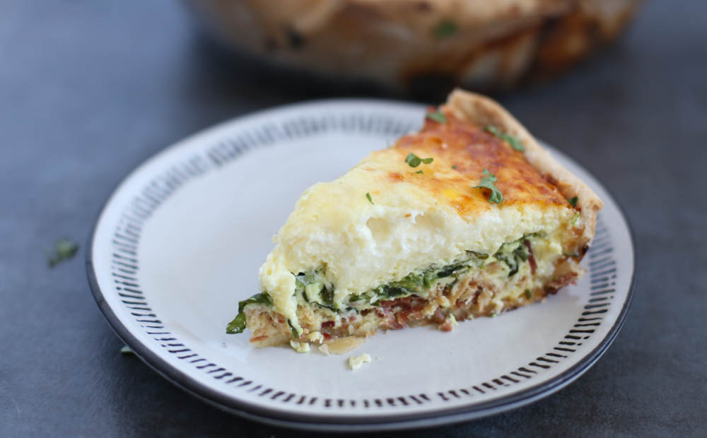 Spinach and bacon quiche slice on a plate