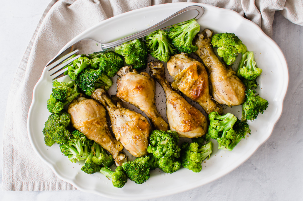 cooked chicken drumsticks on a serving platter with broccoli