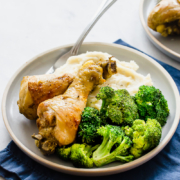 cooked chicken drumsticks on a plate with broccoli and mashed potatoes