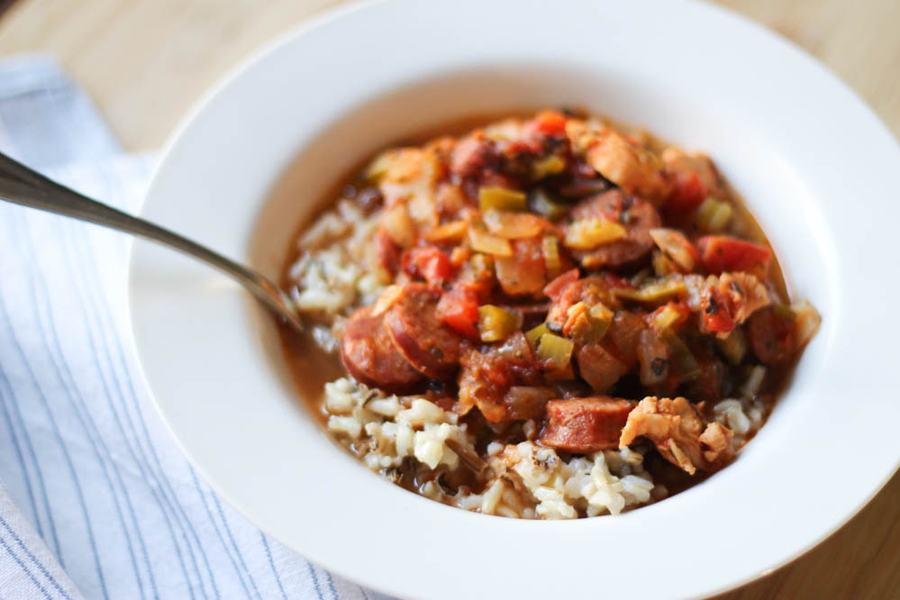 Jambalaya with chicken and andouille sausage over rice in a bowl with a spoon