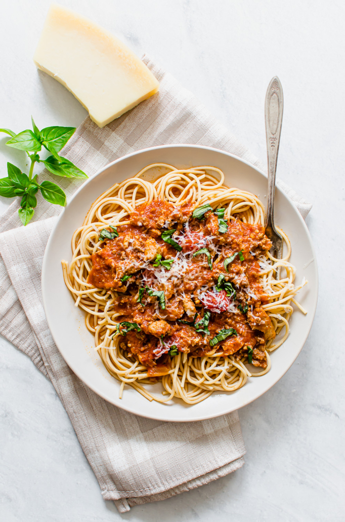 Whole wheat spaghetti with spaghetti sauce and basil on top