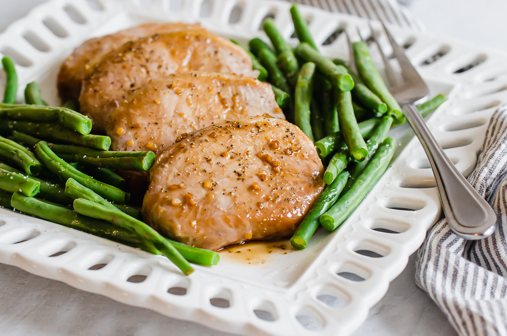 Baked pork chops on a white plate with green beans