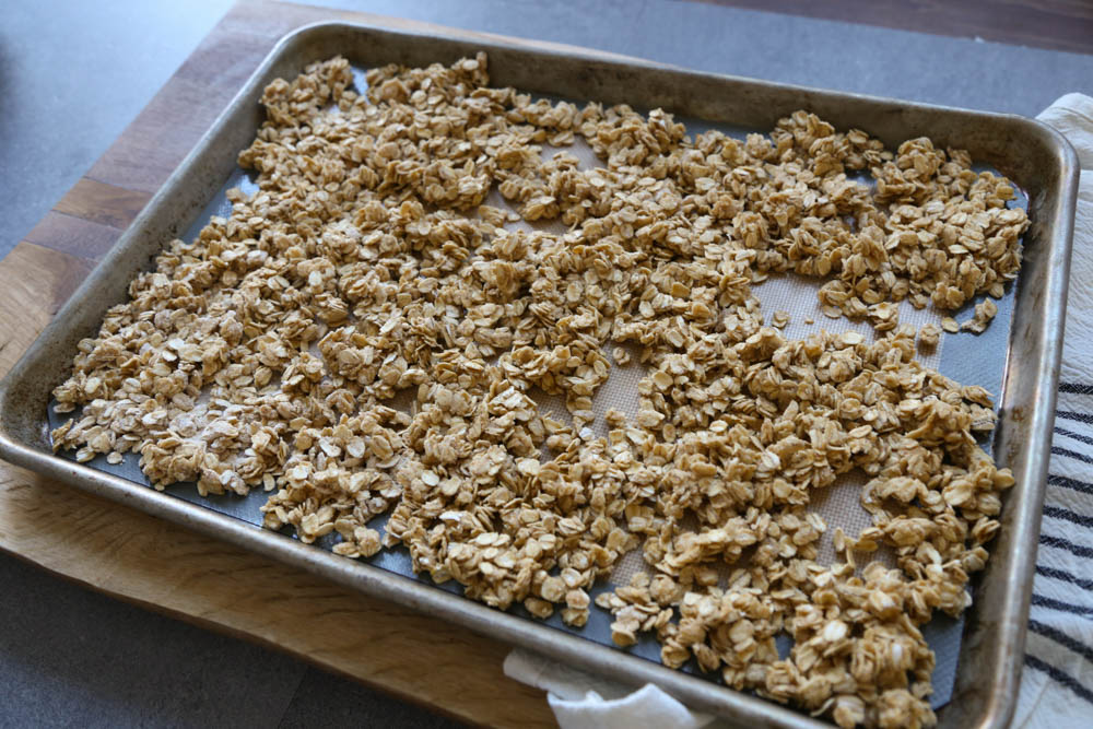 Granola spread out on a sheet pan ready to go in the oven
