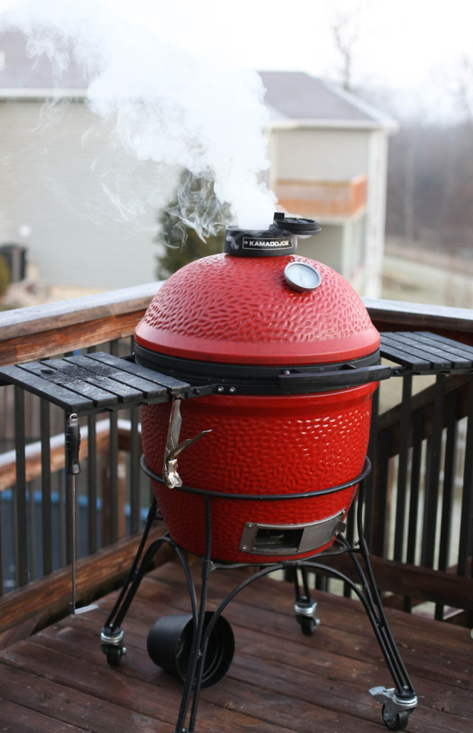 A Kamado Joe with smoke coming out the top