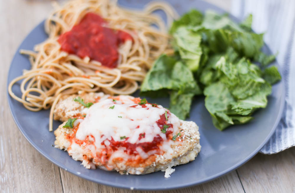 Chicken parmesan on a plate with pasta and a salad