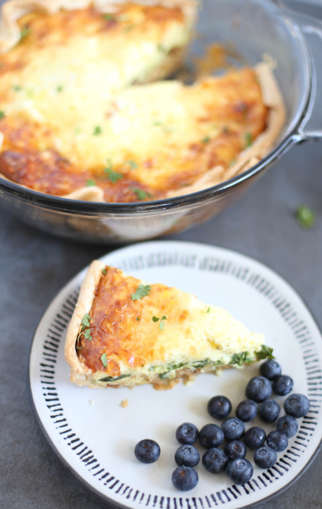 Slice of spinach and bacon quiche on a plate with blueberries