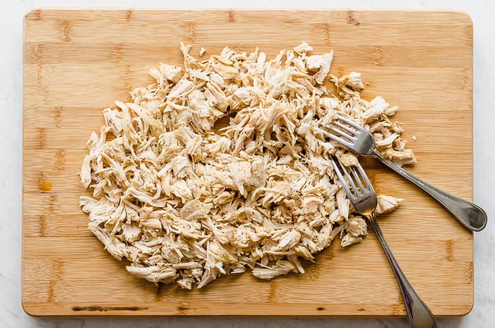 shredded chicken on a wooden cutting board