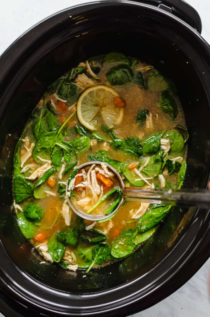 chicken soup being ladled out of the crockpot