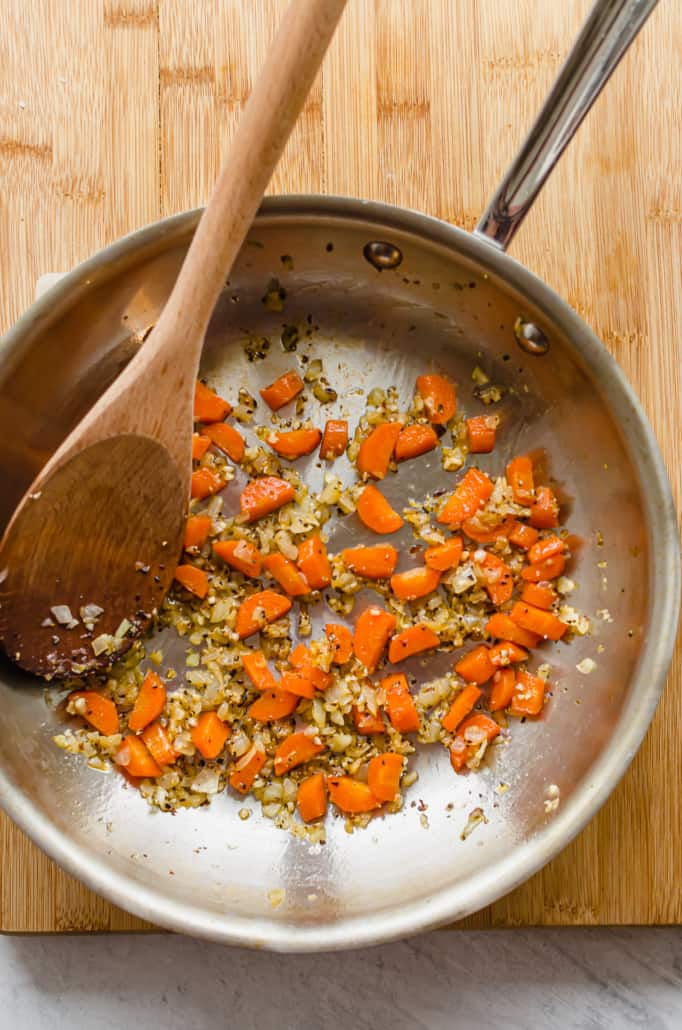 sauteed onions, carrots, and garlic in a pan