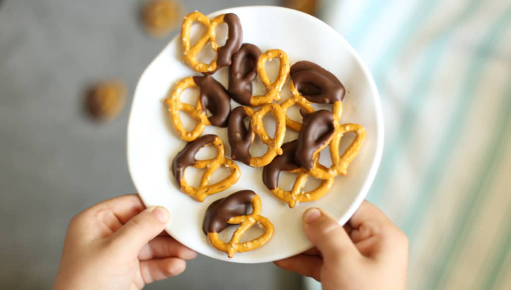 Kids hands holding a plate full of chocolate dipped pretzels