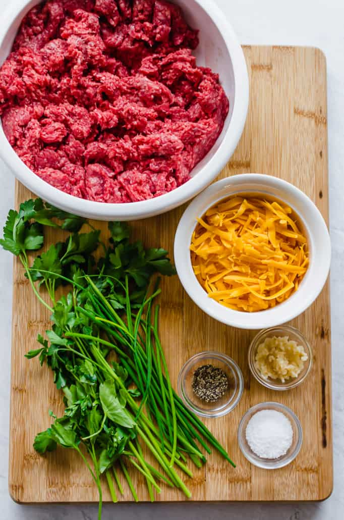 ingredients for cheesy chive burgers, including ground beef, shredded cheese, parsley, chives, garlic, salt, and pepper