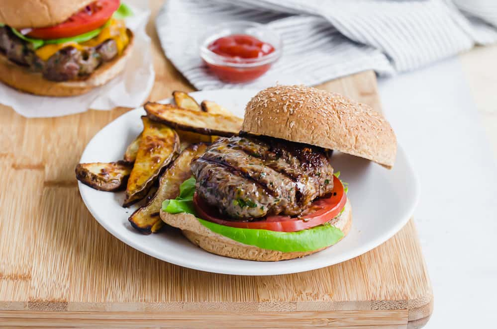 grilled burger on a bun with oven fries on the side