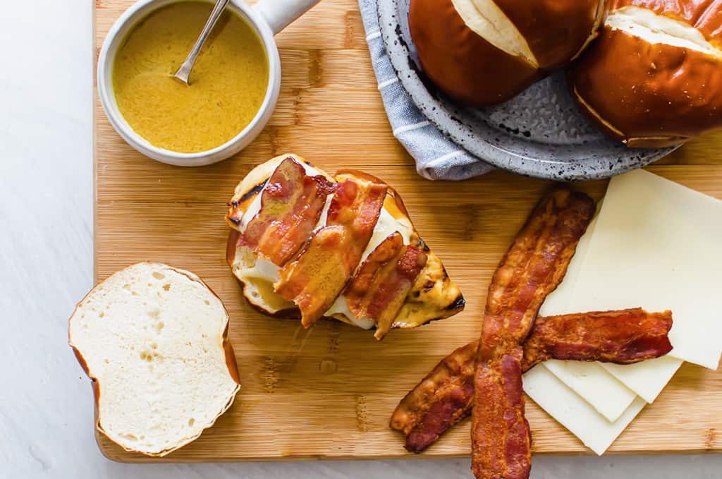 honey dijon chicken sandwich on a pretzel bun with sauce