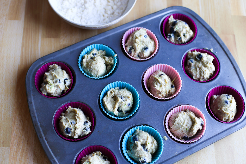 Blueberry avocado muffin batter scooped into silicone muffin liners