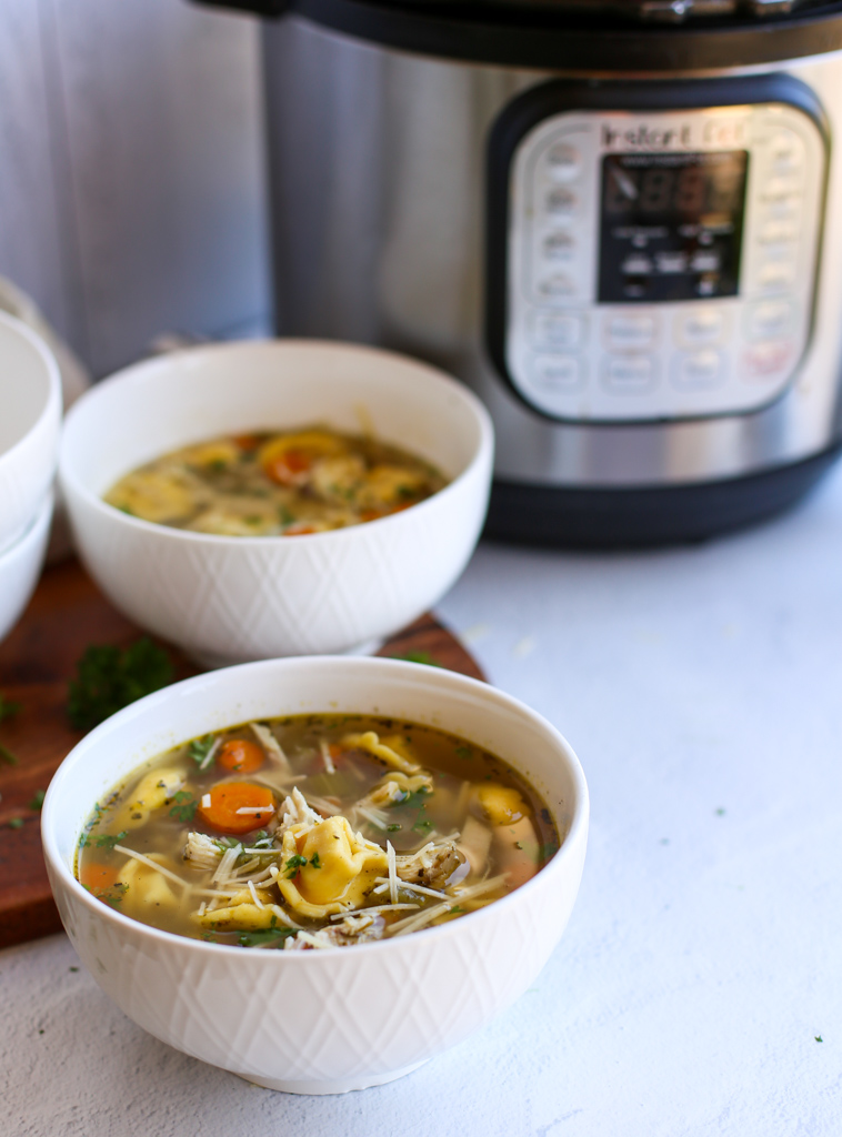 Instant pot tortellini soup in white bowls