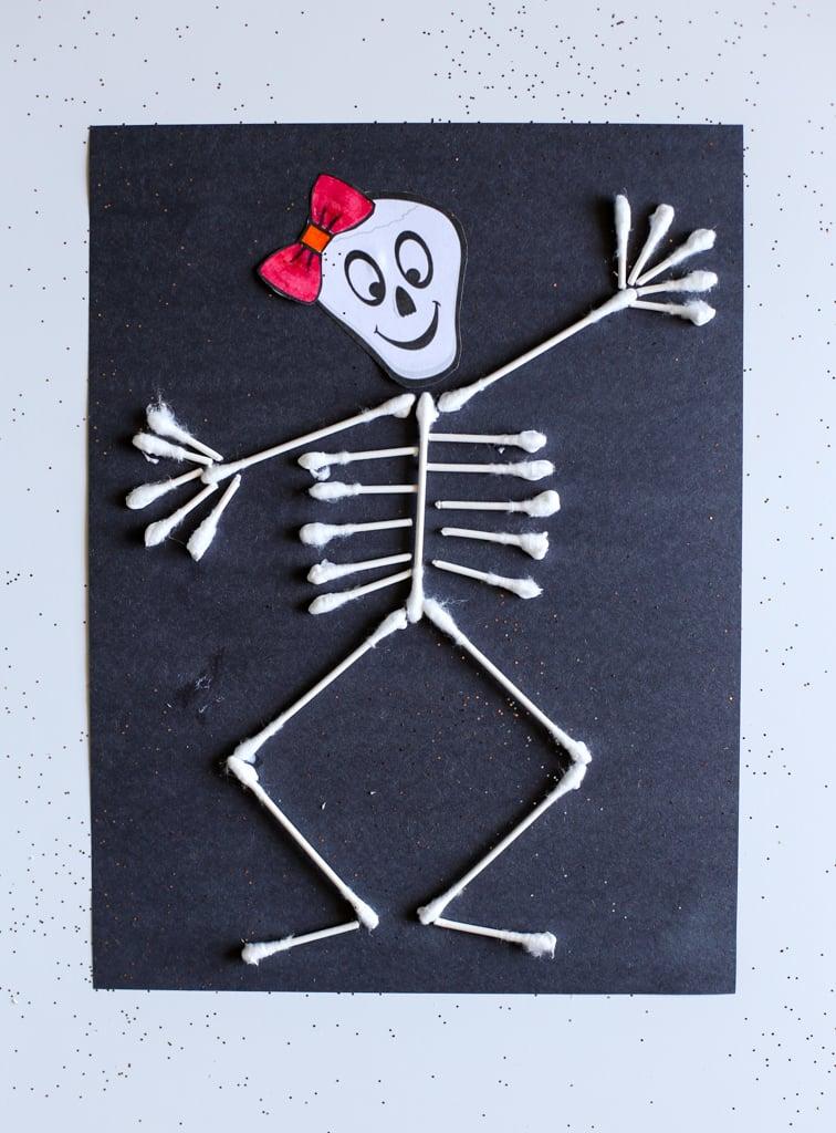 Q-tip skeleton on black construction paper