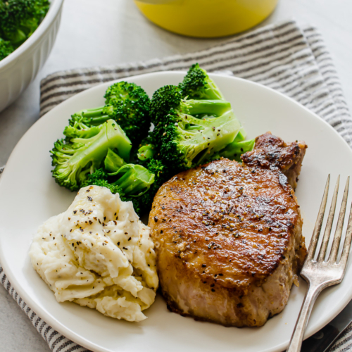 pan seared pork chop on a white plate with mashed potatoes and broccoli
