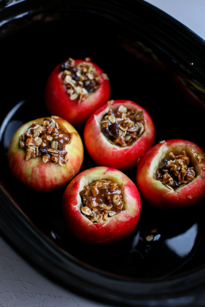 Uncooked apples with a filling in the middle being prepped to cook in the slow cooker