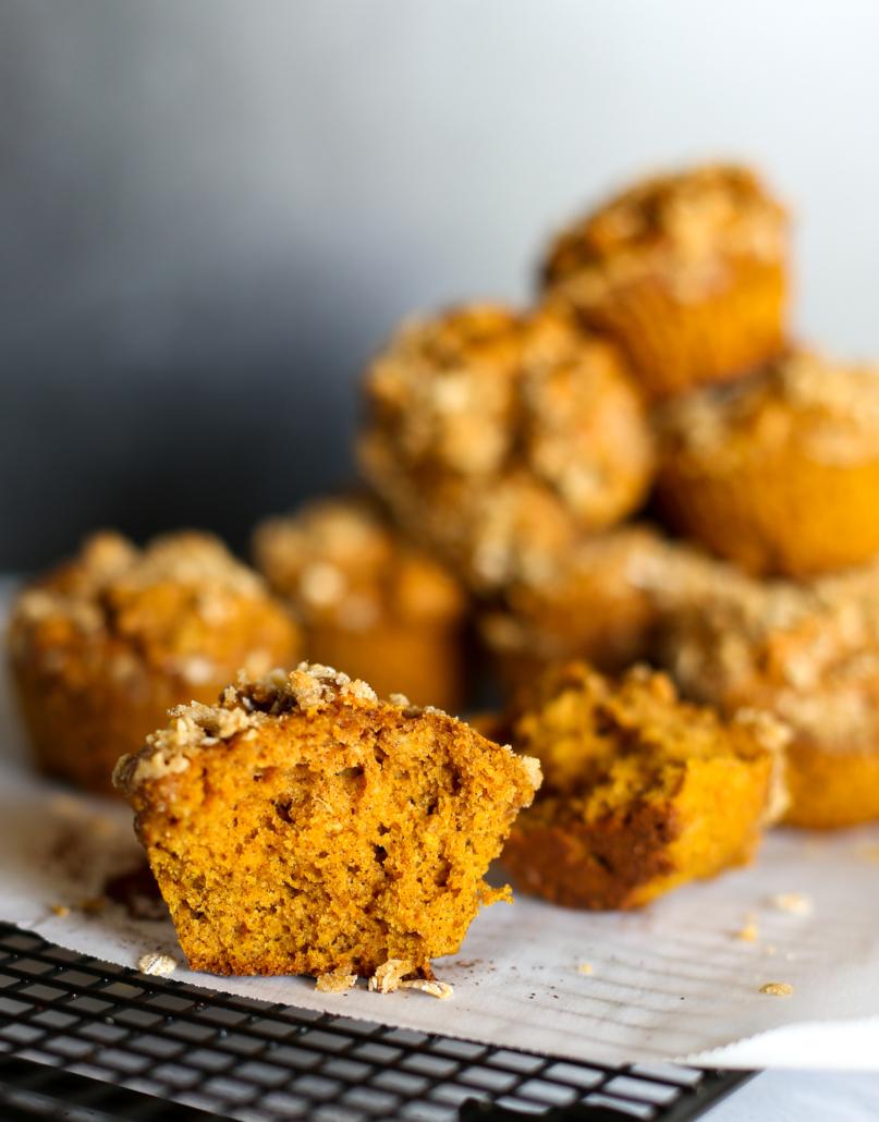 A pumpkin spice muffin cut open with a stack of pumpkin muffins in the background